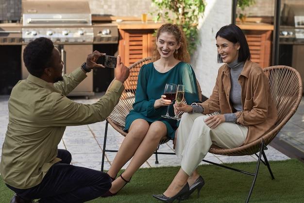 Retrato de corpo inteiro de amigos tirando fotos em um terraço ao ar livre enquanto aproveita a festa,