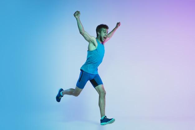 Retrato de corpo inteiro de ativo jovem caucasiano correndo, correndo homem no estúdio gradiente na luz de neon