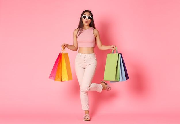 Retrato de corpo inteiro de boba linda garota asiática em óculos de sol esporte incrível promoção de venda na loja, correndo para fazer compras com uma expressão curiosa e animada, carregar sacolas de compras, parede rosa.