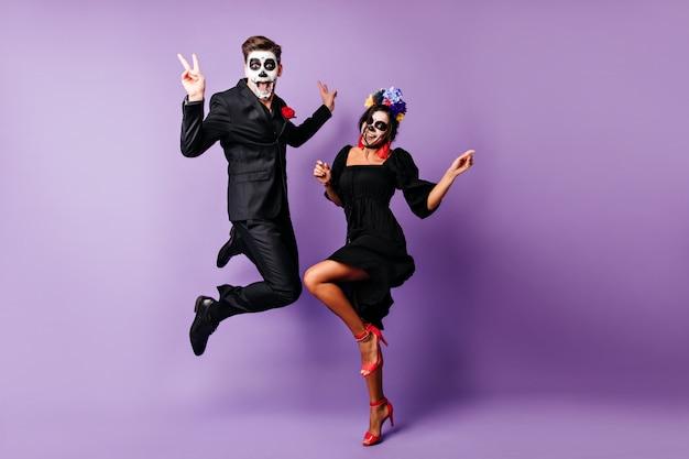 Retrato de corpo inteiro de casal europeu dançando sobre fundo roxo em fantasias de zumbi. jovens engraçados brincando no evento de halloween.