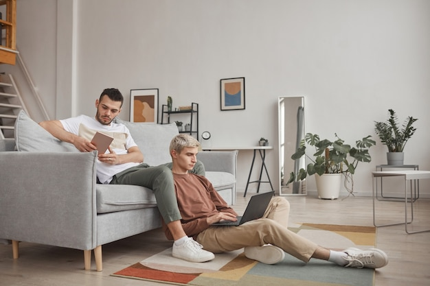 Retrato de corpo inteiro de casal gay contemporâneo usando computadores enquanto relaxam no sofá juntos em um interior mínimo de casa, copie o espaço