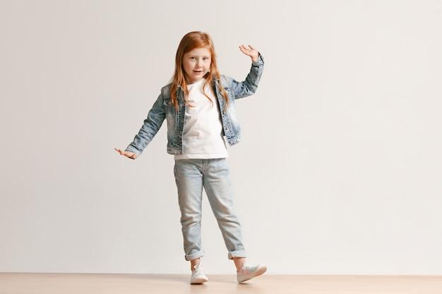 Retrato de corpo inteiro de criança bonitinha em roupas elegantes jeans sorrindo
