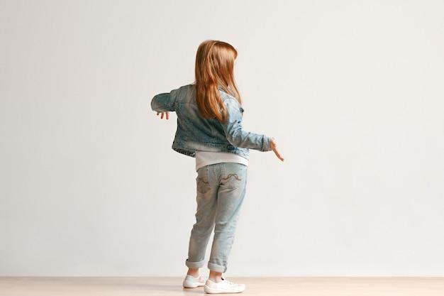 Retrato de corpo inteiro de criança menina bonitinha com roupas jeans elegantes, de pé contra a parede branca do estúdio. conceito de moda infantil