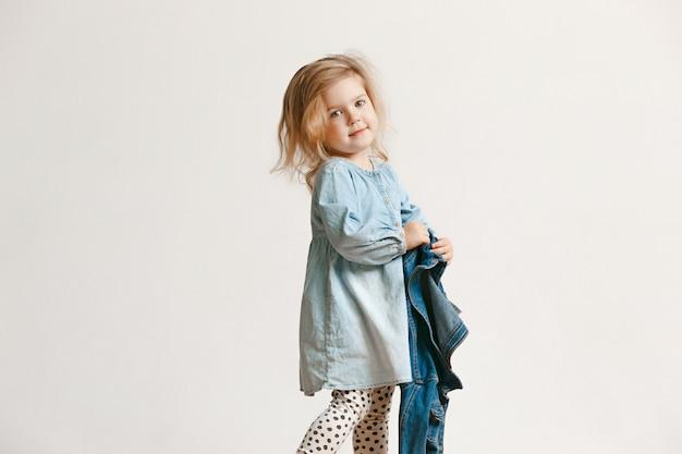 Retrato de corpo inteiro de criança menina bonitinha com roupas jeans elegantes e sorrindo, de pé em branco. conceito de moda infantil