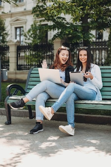 Retrato de corpo inteiro de dois amigos sentados em um banco rindo