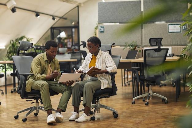 Retrato de corpo inteiro de dois empresários afro-americanos contemporâneos discutindo projeto de trabalho enquanto estão sentados em cadeiras em um escritório moderno, copie o espaço