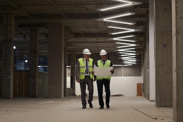 Retrato de corpo inteiro de dois empresários vestindo capacetes e segurando planos enquanto caminham em direção à câmera no canteiro de obras,