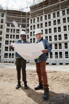 Retrato de corpo inteiro de dois engenheiros discutindo plantas baixas no canteiro de obras