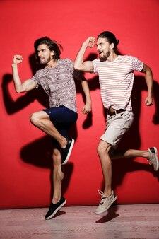 Retrato de corpo inteiro de dois jovens irmãos gêmeos alegres