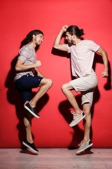 Retrato de corpo inteiro de dois jovens irmãos gêmeos felizes