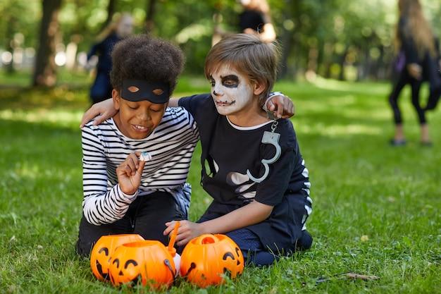 Retrato de corpo inteiro de dois meninos vestindo fantasias de halloween sentados na grama verde ao ar livre com baldes de doces, copie o espaço