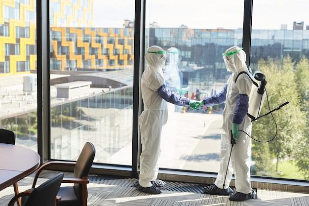 Retrato de corpo inteiro de dois trabalhadores de desinfecção vestindo ternos contra materiais perigosos, apertando as mãos em pé contra a janela do escritório,