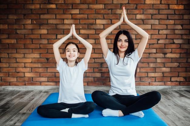Retrato de corpo inteiro de duas garotas atraentes malhando em casa, fazendo exercícios de ioga na esteira azul, sentado no easy, na esteira azul