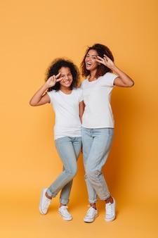 Retrato de corpo inteiro de duas irmãs africanas felizes em pé