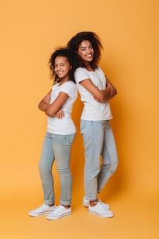 Retrato de corpo inteiro de duas irmãs africanas felizes
