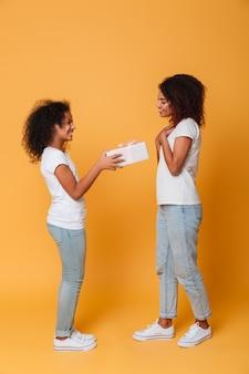 Retrato de corpo inteiro de duas irmãs afro-americanas alegres