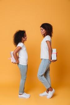 Retrato de corpo inteiro de duas irmãs afro-americanas felizes