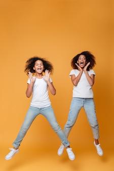Retrato de corpo inteiro de duas irmãs afro-americanas pulando
