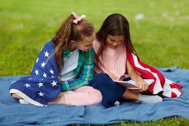 Retrato de corpo inteiro de duas lindas garotas cobertas pela bandeira americana, sentadas na manta de piquenique no parque e lendo um livro