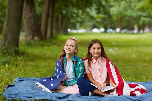 Retrato de corpo inteiro de duas lindas garotas cobertas pela bandeira americana, sentadas na manta de piquenique no parque e sorrindo