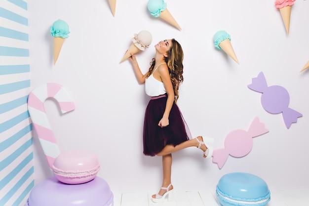 Retrato de corpo inteiro de elegante garota bem-aventurada de pé em uma perna e segurando o sorvete. mulher jovem incrível vestindo saia violeta exuberante e sandálias de salto, se divertindo na festa temática.