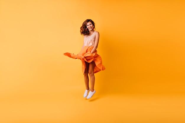 Retrato de corpo inteiro de elegante senhora elegante pulando no estúdio. linda garota ruiva com saia laranja se divertindo.