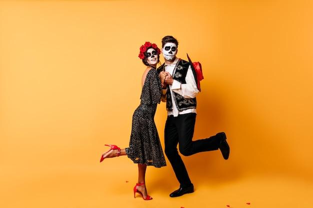 Retrato de corpo inteiro de engraçados zumbis dançando. foto interna de casal morto comemorando o dia das bruxas juntos.