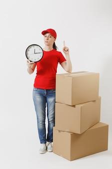 Retrato de corpo inteiro de entregadora de boné vermelho, camiseta isolado no fundo branco. correio feminino perto de caixas de papelão vazias, segurando o relógio redondo, mostrando a tempo. recebendo pacote. copie o espaço.