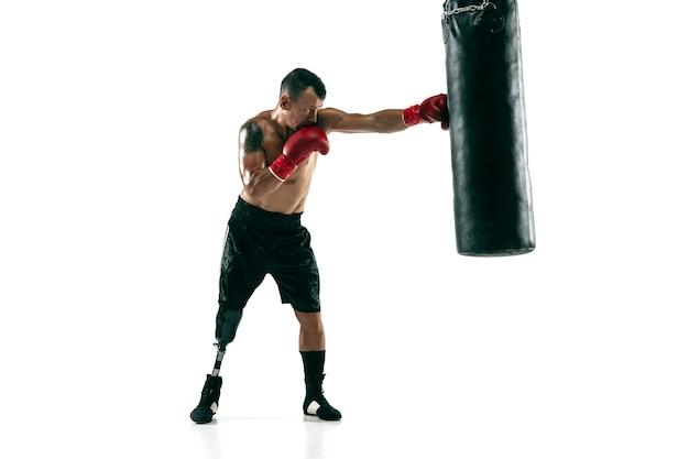 Retrato de corpo inteiro de esportista musculoso com perna protética, copie o espaço. boxeador masculino em luvas vermelhas, treinando e praticando. isolado na parede branca. conceito de esporte, estilo de vida saudável. Foto gratuita