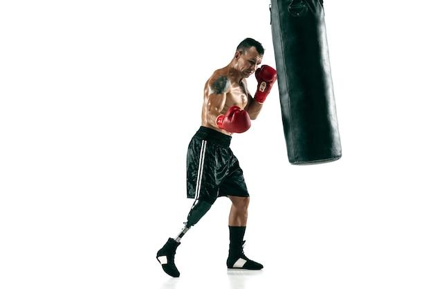 Retrato de corpo inteiro de esportista musculoso com perna protética, copie o espaço. boxeador masculino em luvas vermelhas, treinando e praticando. isolado na parede branca. conceito de esporte, estilo de vida saudável.