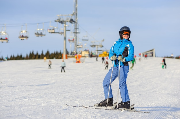 Retrato de corpo inteiro de esquiador de mulher em pé em uma pista de esqui