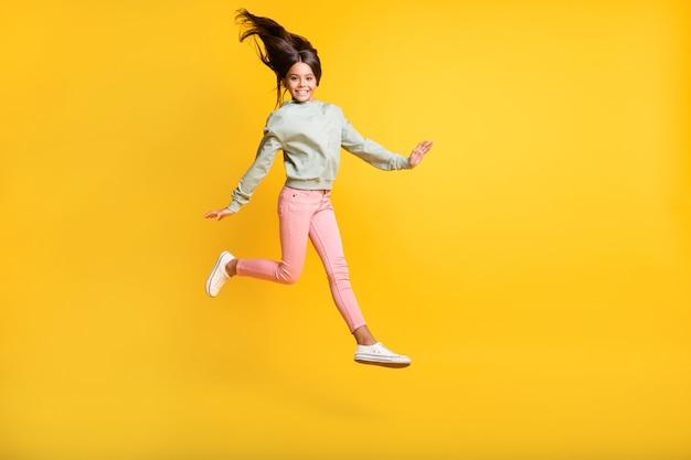 Retrato de corpo inteiro de estudante pulando felicidade de voar de cabelo isolado em um fundo de cor amarela brilhante