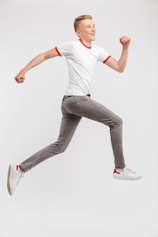 Retrato de corpo inteiro de feliz caucasiano adolescente 16-18 anos de idade em streetwear sorrindo durante a execução, isolado sobre o branco