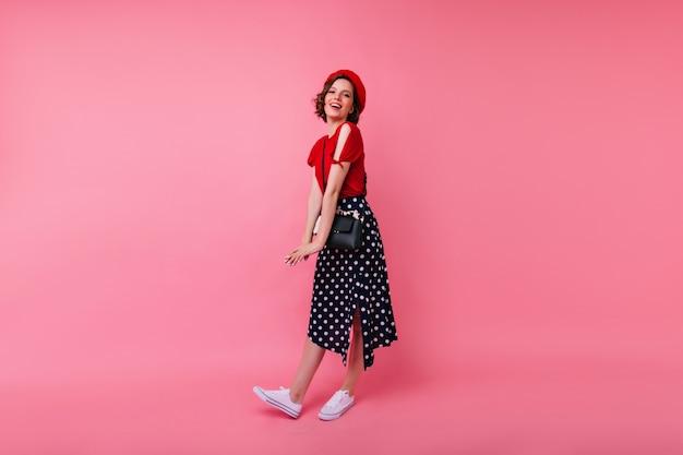 Retrato de corpo inteiro de feliz mulher europeia em calçados esportivos brancos. rindo garota alegre na boina vermelha francesa.