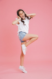 Retrato de corpo inteiro de garota energética de 8 a 10 anos em roupas casuais cantando e dançando enquanto ouve música por meio de fones de ouvido sem fio, isolado sobre um fundo rosa