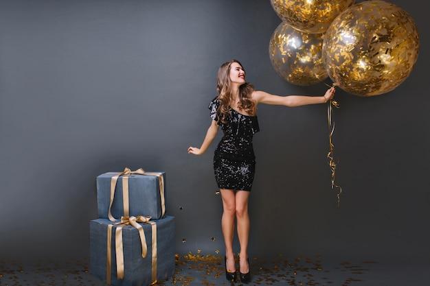 Retrato de corpo inteiro de garota europeia refinada usa vestido preto na festa de aniversário. feliz senhora de cabelos compridos com balões mal pode esperar para abrir os presentes.
