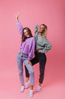 Retrato de corpo inteiro de garotas maravilhosas com roupa de rua vintage. senhoras na moda caucasianas dançando na rosa.