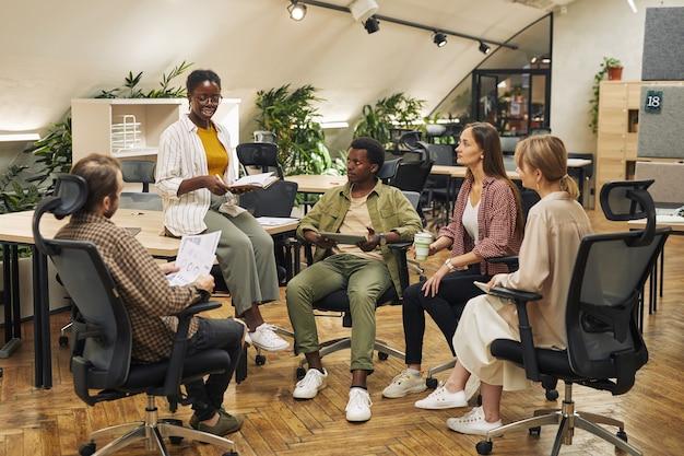 Retrato de corpo inteiro de grupo multiétnico de jovens discutindo projeto de trabalho enquanto está sentado em círculo em um escritório moderno e ouvindo a gerente feminina