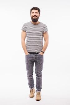Retrato de corpo inteiro de homem barbudo em uma camisa com o braço no bolso que aponta para longe.