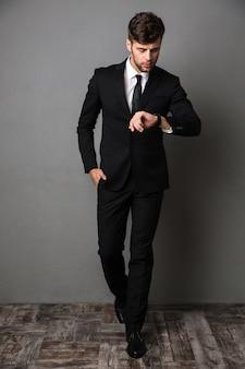 Retrato de corpo inteiro de homem confiante em terno preto clássico, verificando o tempo em seu relógio de pulso