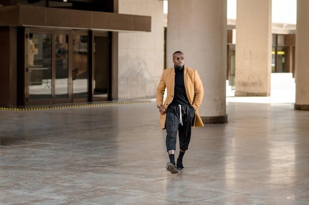 Retrato de corpo inteiro de homem de negócios africano jovem caminhando ao ar livre.