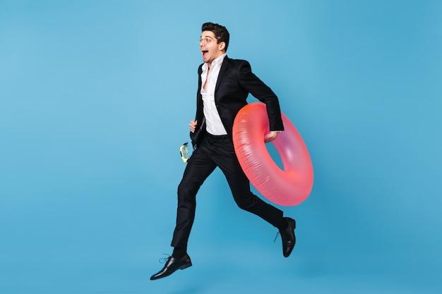 Retrato de corpo inteiro de homem em roupa de negócios, executando no espaço azul com círculo inflável rosa.