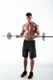 Retrato de corpo inteiro de homem forte de esportes atléticos treinando com halteres