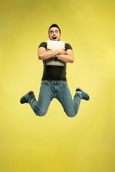 Retrato de corpo inteiro de homem pulando feliz com dispositivos isolados em amarelo.