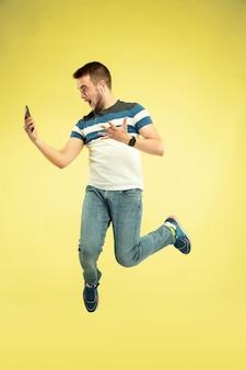Retrato de corpo inteiro de homem pulando feliz com gadgets em amarelo.