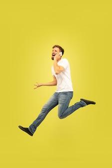 Retrato de corpo inteiro de homem pulando feliz isolado em fundo amarelo. modelo masculino caucasiano com roupas casuais. liberdade de escolha, inspiração, conceito de emoções humanas. apresse-se, falando no telefone.