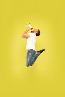 Retrato de corpo inteiro de homem pulando feliz isolado em fundo amarelo. modelo masculino caucasiano com roupas casuais. liberdade de escolha, inspiração, conceito de emoções humanas. chamando com paz na boca.