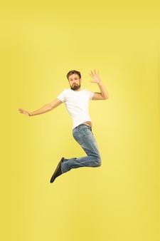 Retrato de corpo inteiro de homem pulando feliz isolado em fundo amarelo. modelo masculino caucasiano com roupas casuais. liberdade de escolha, inspiração, conceito de emoções humanas. dá cinco, cumprimenta, confiante.