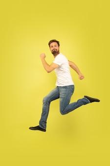 Retrato de corpo inteiro de homem pulando feliz isolado em fundo amarelo. modelo masculino caucasiano com roupas casuais. liberdade de escolha, inspiração, conceito de emoções humanas. fugindo feliz.