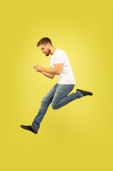 Retrato de corpo inteiro de homem pulando feliz isolado em fundo amarelo. modelo masculino caucasiano com roupas casuais. liberdade de escolha, inspiração, conceito de emoções humanas. ganhar na aposta desportiva.